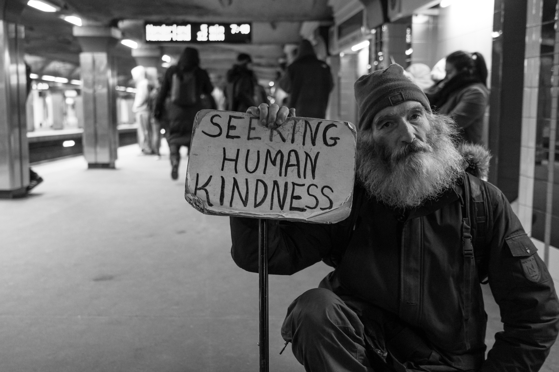 Homeless man with sign saying seeking human kindness