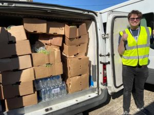 a support worker stands next to a trolly of supplies with his thumbs up