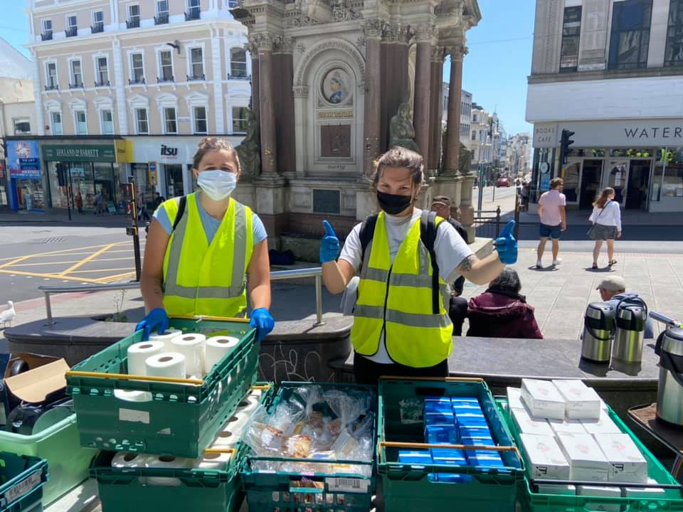 two homeless support volunteers stand next to donations with thier thumbs up.